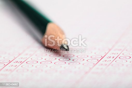 806639724 istock photo School Students hands taking exams, writing examination holding pencil on optical form of standardized test with answers sheet doing final exam in classroom. Education assessment Concept. Soft focus 1138245682