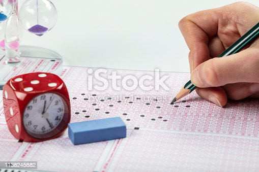806639724 istock photo School Students hands taking exams, writing examination holding pencil on optical form of standardized test with answers sheet doing final exam in classroom. Education assessment Concept. Soft focus 1138245882