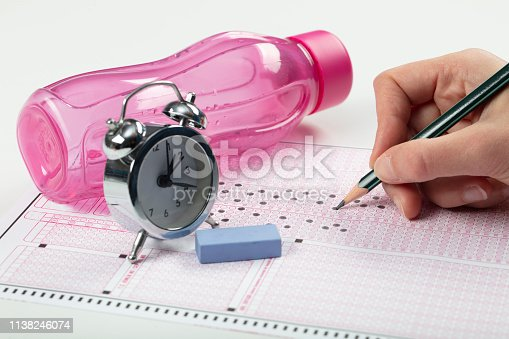 806639724 istock photo School Students hands taking exams, writing examination holding pencil on optical form of standardized test with answers sheet doing final exam in classroom. Education assessment Concept. Soft focus 1138246074
