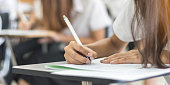 istock School student's taking exam, thinking hard, writing answer in classroom for educational university admission test  and world literacy day concept 963195608