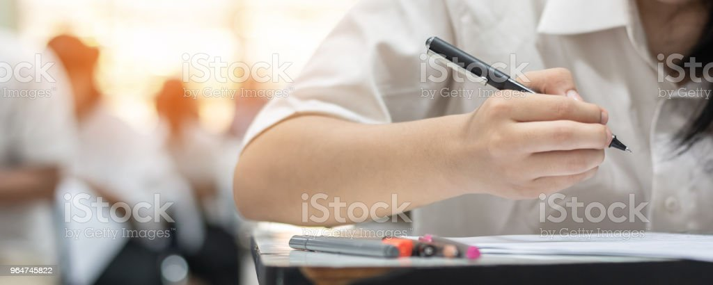 School student's taking exam, thinking hard, writing answer in classroom for educational university admission test  and world literacy day concept royalty-free stock photo