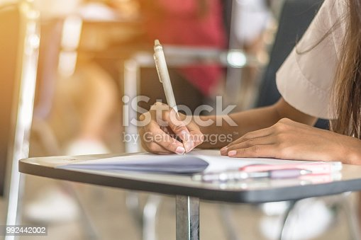 963192098 istock photo School student's taking exam writing answer in classroom for education and literacy concept 992442002
