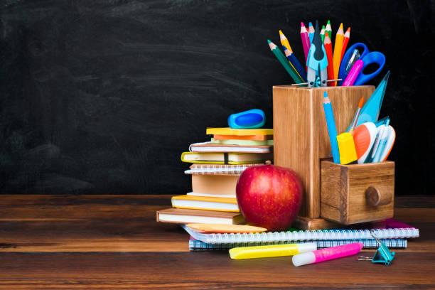 学校用品、黒板の背景の上の木製のテーブルの上のアクセサリー - 学校の文房具 ストックフォトと画像
