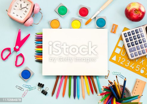 istock School supplies and blank paper on blue background. Back to school concept 1170584978