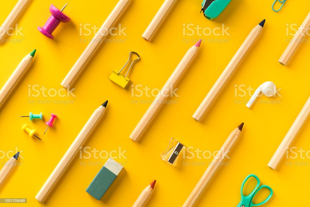 School supplies and coloring pencils flat lay on yellow background royalty-free stock photo