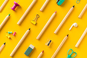 School supplies and coloring pencils flat lay on yellow background