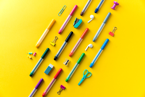 School supplies and coloring pens on yellow background. Back to school colorful flat lay