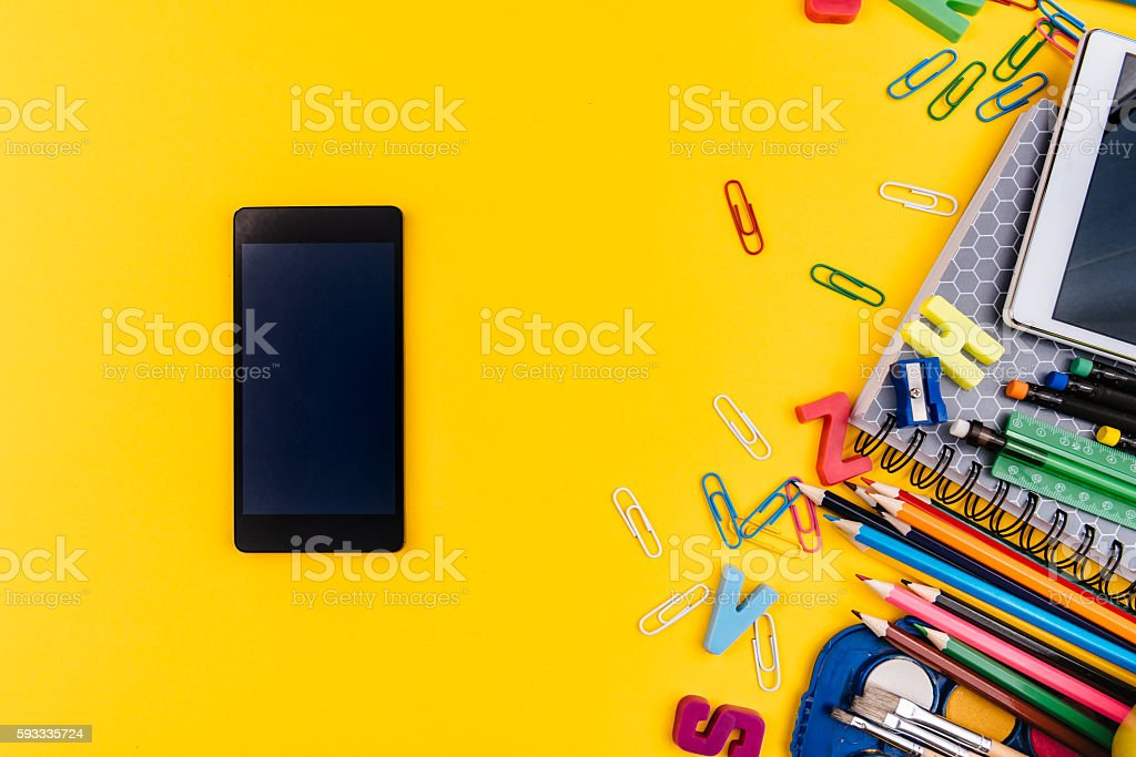 School supplies and mobile phone on yellow background stock photo