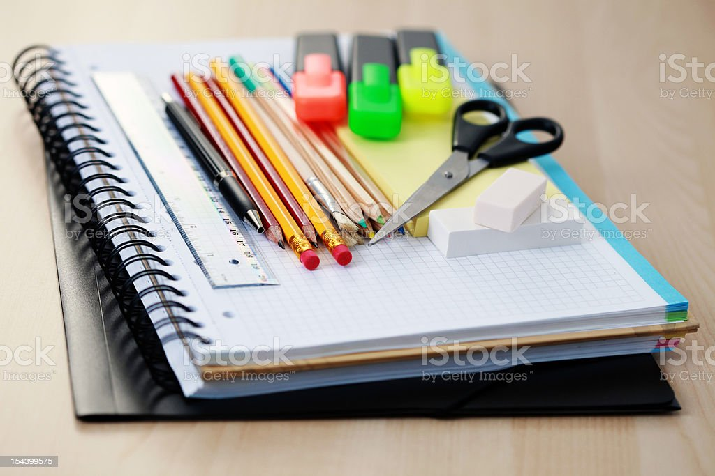 School supplies arranged on a stack of notebooks royalty-free stock photo