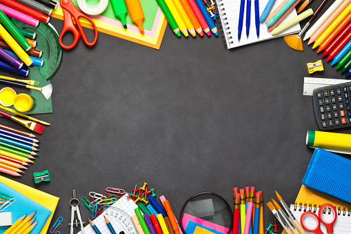 Black chalkboard with school supplies making a border. The composition includes books, note pad, paper clips, yellow pencils, note pad, loupe, paintbrushes, watercolors, crayons, eraser, pencil sharpener, scissors, compass, ruler, calculator and pushpins. Useful copy space left at the center of the frame. High angle view DSRL studio photo taken with Canon EOS 5D Mk II and Canon EF 100mm f/2.8L Macro IS USM