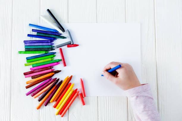 útiles escolares para dibujar sobre la mesa: papel y lápices de colores. un niño sostiene un lápiz en sus manos - dibujar fotografías e imágenes de stock