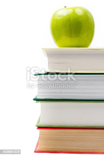 153178960istockphoto School supplies in classroom with books and apple 453684329