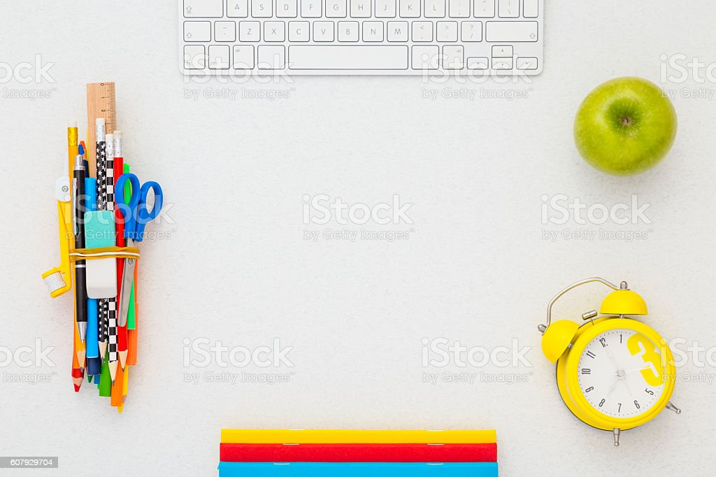 School supplies, keyboard, alarm clock and apple with copy space. stock photo