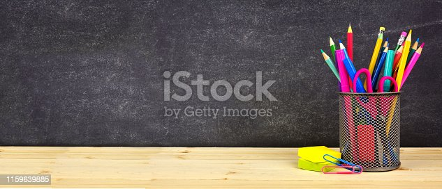 istock School supplies on a wood desk with chalkboard background. Back to school. Copy space. Banner. 1159639885