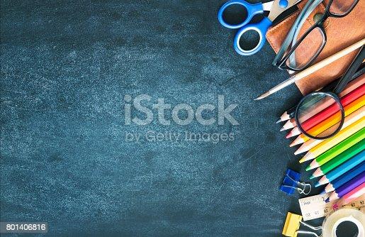 istock School supplies on black board background empty copy space. 801406816