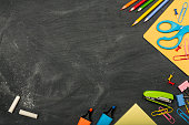 School supplies on blackboard with chalk and copy space