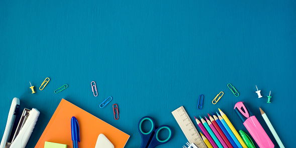 School supplies on blue background. Top view. Banner with copy space.