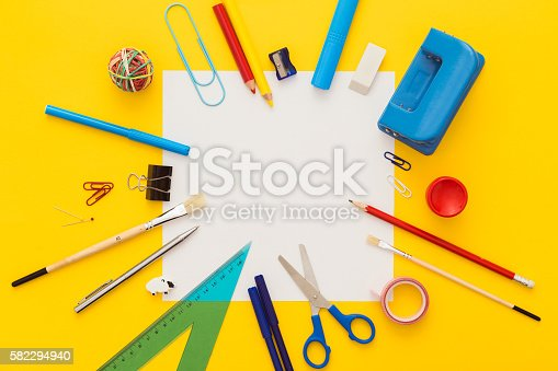 istock School supplies on yellow desk with copy space.Top view. 582294940