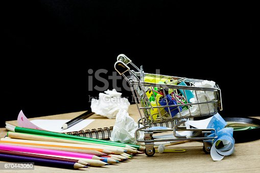 istock School Supplies with shopping cart on wood, black background. 670443080