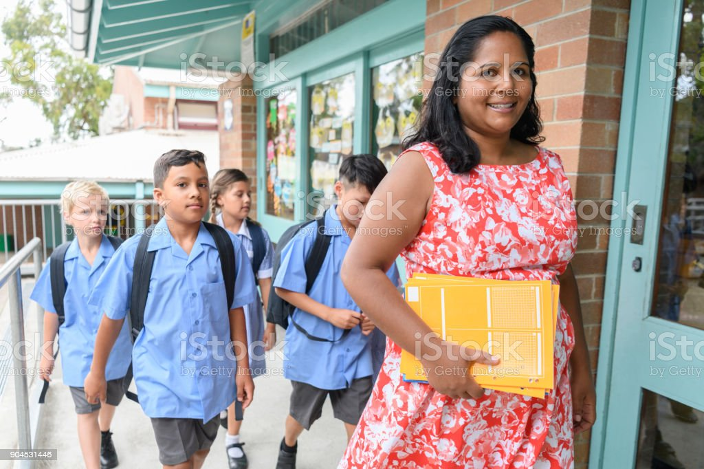 School teacher and pupils arriving at school stock photo
