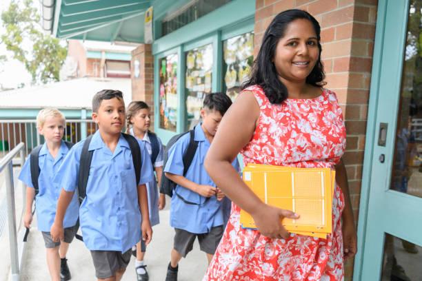 School teacher and pupils arriving at school stock photo