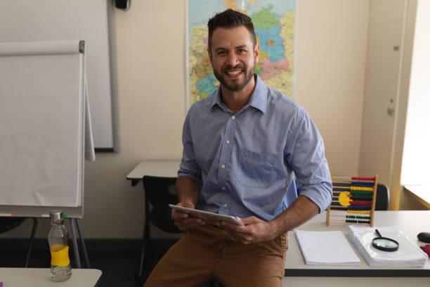 Schullehrer Blick in die Kamera und sitzen am Schreibtisch im Klassenzimmer – Foto
