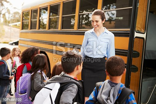 1031397608 istock photo School teacher preparing kids to get on the school bus 1031391122