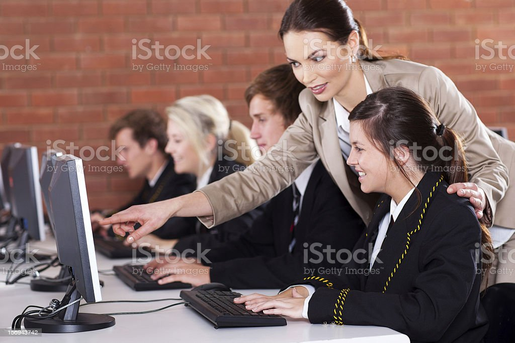 school teacher teaching in computer room stock photo