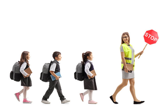 School teacher with a safety vest and stop sign walking with schoolchildren stock photo