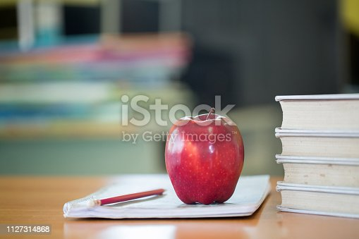 istock School teacher's desk with stack of books and apple, Educational concept. 1127314868