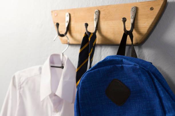 School uniform and schoolbag hanging on hook stock photo