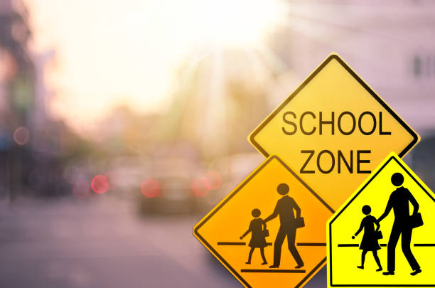 School zone warning sign on blur traffic road with colorful bokeh light abstract background. Copy space of transportation and travel concept. Vintage tone color style. School zone warning sign on blur traffic road with colorful bokeh light abstract background. Copy space of transportation and travel concept. Vintage tone color style. time zone stock pictures, royalty-free photos & images
