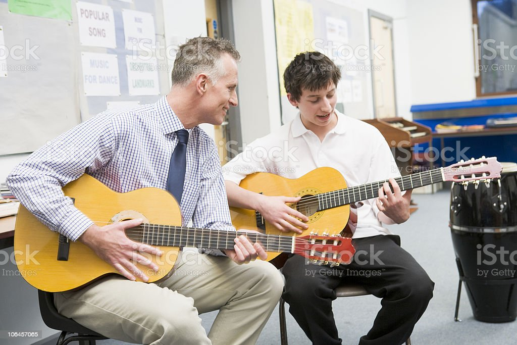 Schoolboy and Teacher Playing Guitar in Music Class stock photo