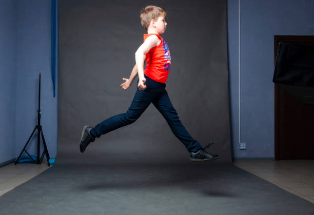 Schoolboy backstage photo shoot. Jump in the air stock photo