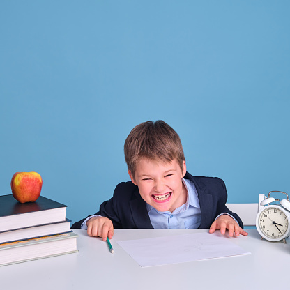 Schoolboy boy in uniform with textbooks and pen laughs while sitting at a school desk, blue background