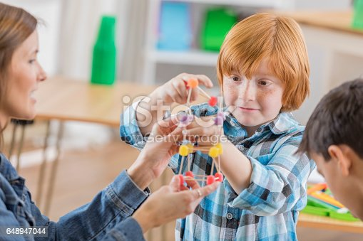 648947070 istock photo Schoolboy concentrates while building something in science class 648947044