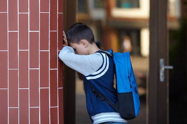 Schoolboy cries in the yard of the school leaning against the wall stock photo
