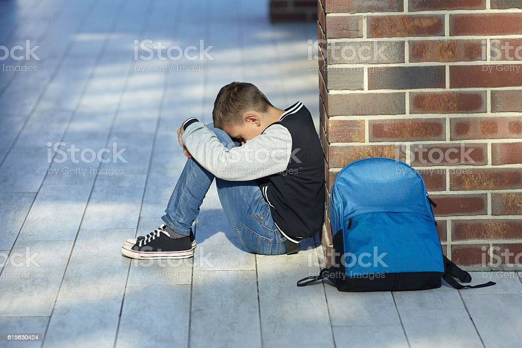 schoolboy crying in the hallway of the school - foto de stock