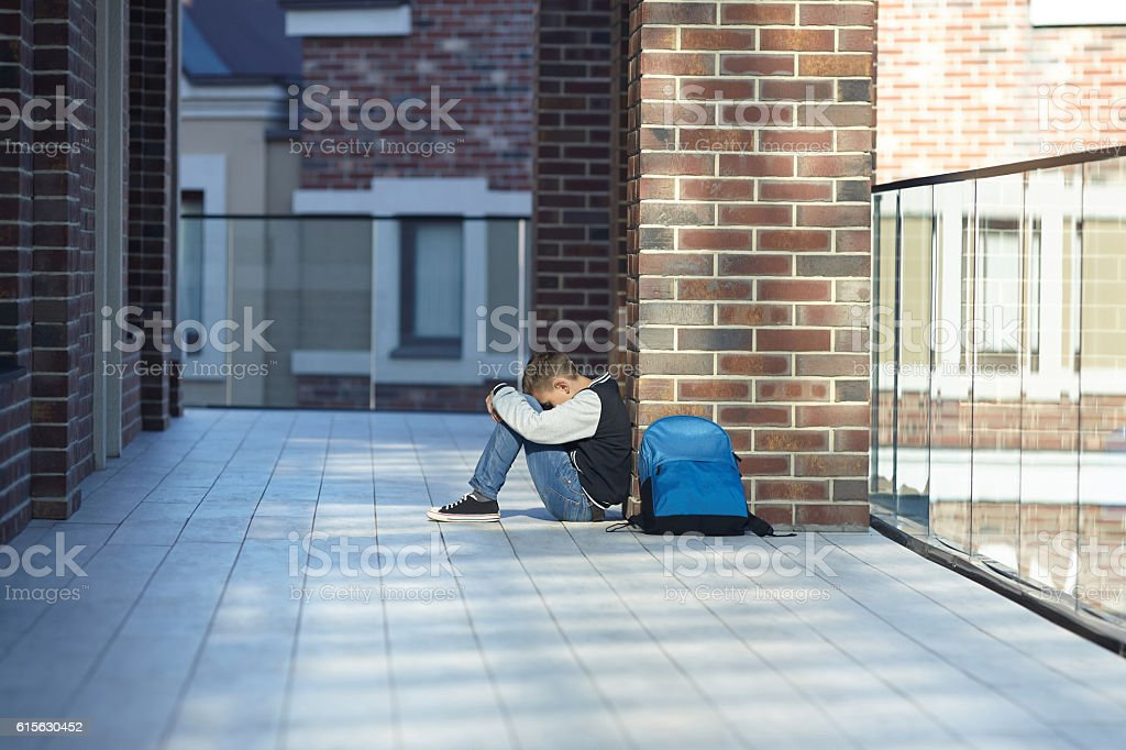 schoolboy crying in the hallway of the school stock photo