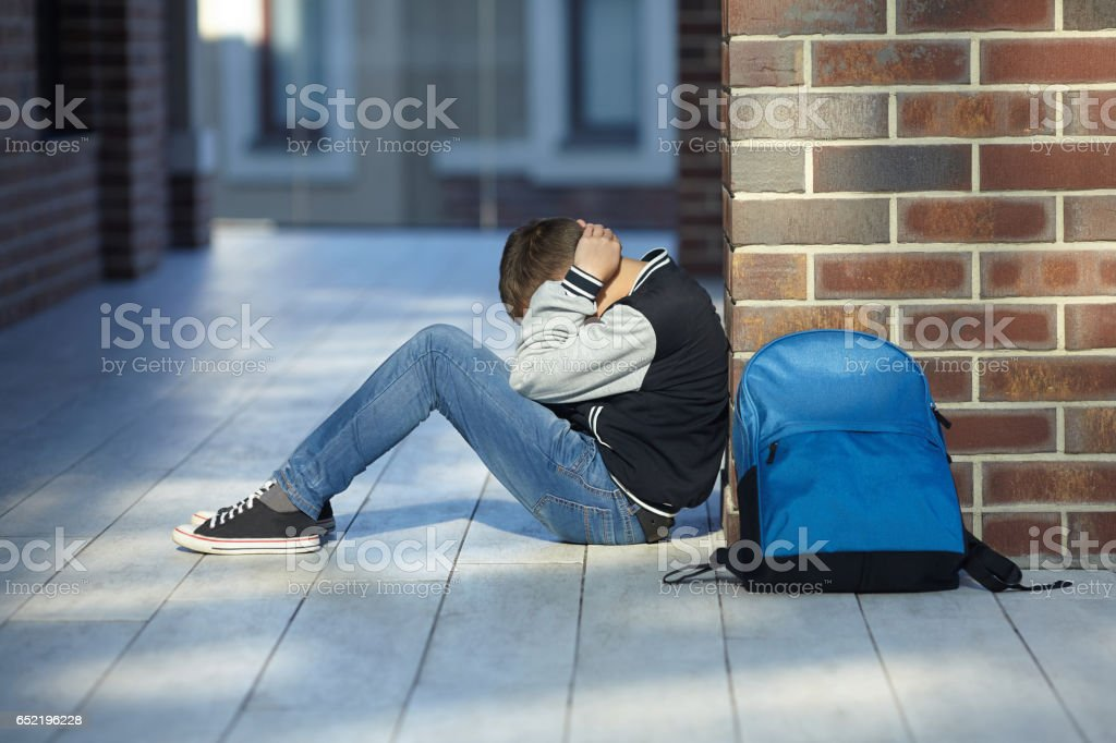 schoolboy crying in the hallway of the school schoolboy crying in the hallway of the school, negative emotion Adolescence Stock Photo