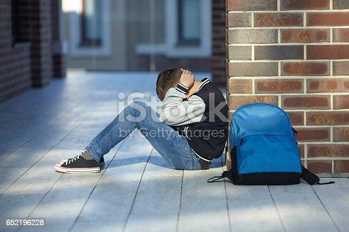 istock schoolboy crying in the hallway of the school 652196228