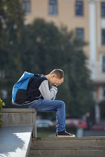 schoolboy crying on the street stock photo