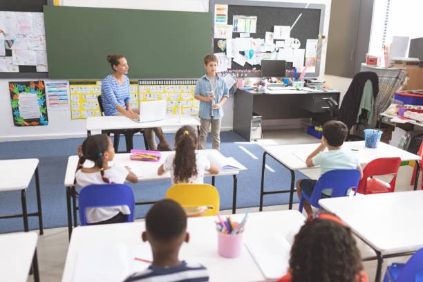 Schuljunge erklärt vor seinen Klassenkameraden die Windmühle, während ihr Lehrer ihm zuhört – Foto
