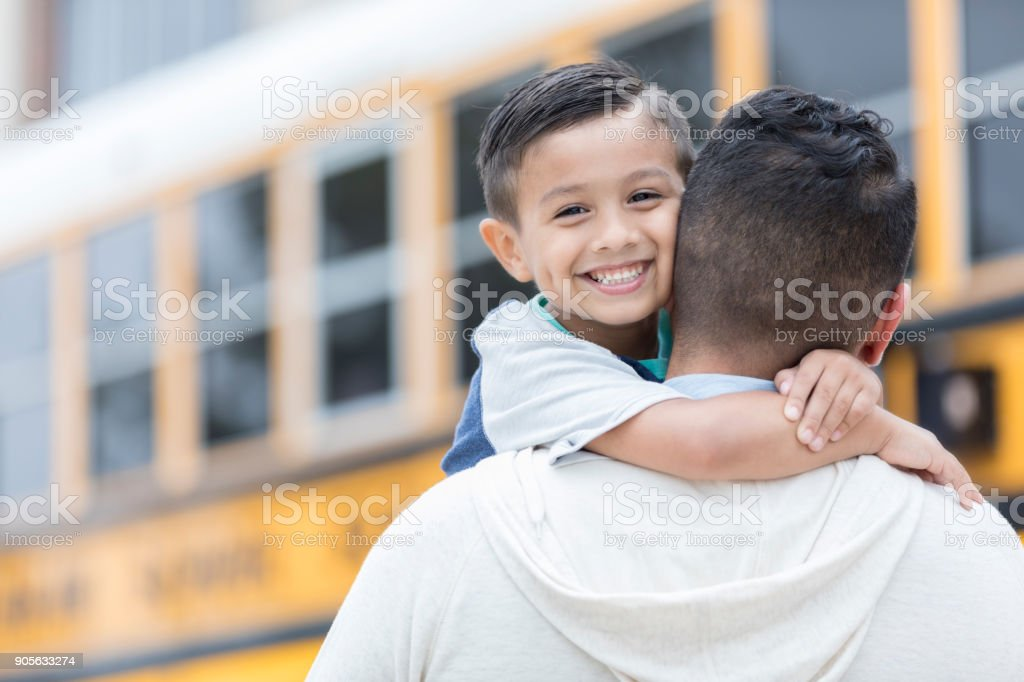 Schoolboy greets father after first day stock photo
