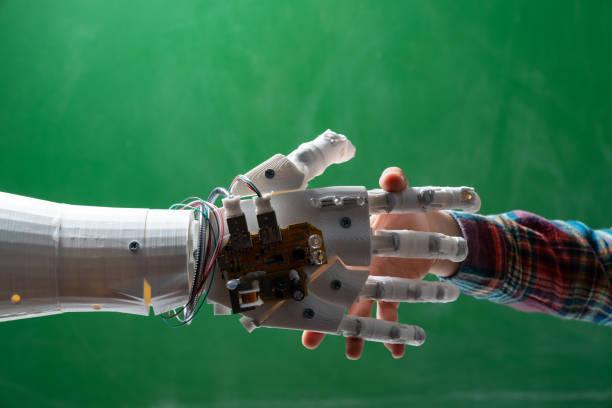 Schoolboy Handshaking Humanoid Robotic Hand On green Chalkboard stock photo