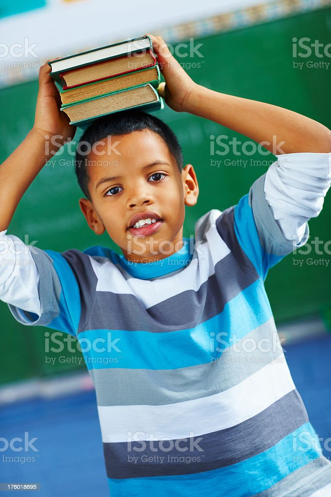 Schoolboy holding a stack of books on his head royalty-free stock photo