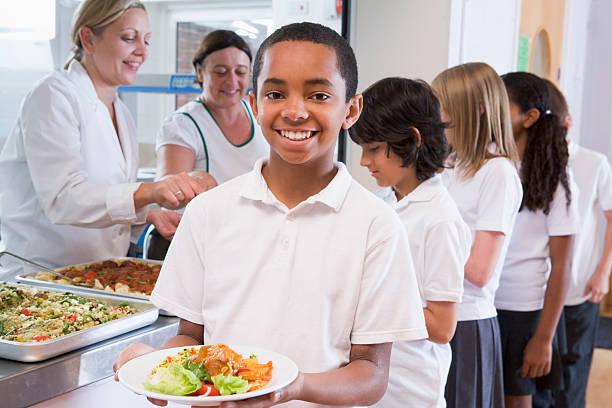 schulkind-nur jungen hält teller mit mittagessen in der cafeteria der schule - kantine stock-fotos und bilder