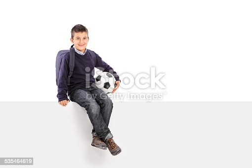 istock Schoolboy holding soccer ball seated on a panel 535464619