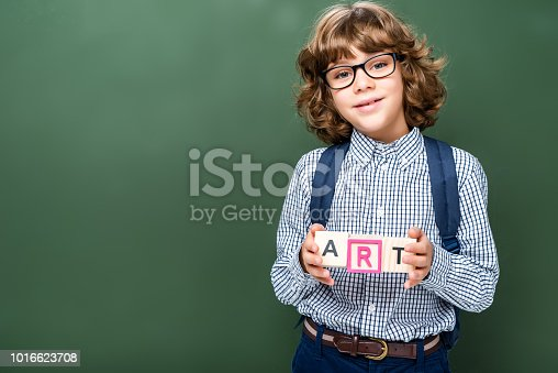 1016623732istockphoto schoolboy holding wooden cubes with word art near blackboard 1016623708