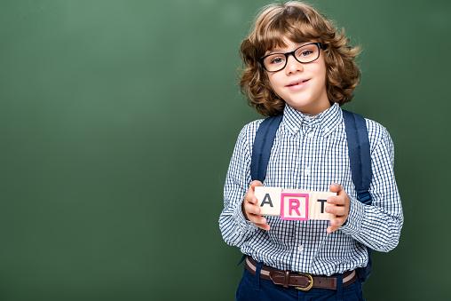 1016623732 istock photo schoolboy holding wooden cubes with word art near blackboard 1016623708